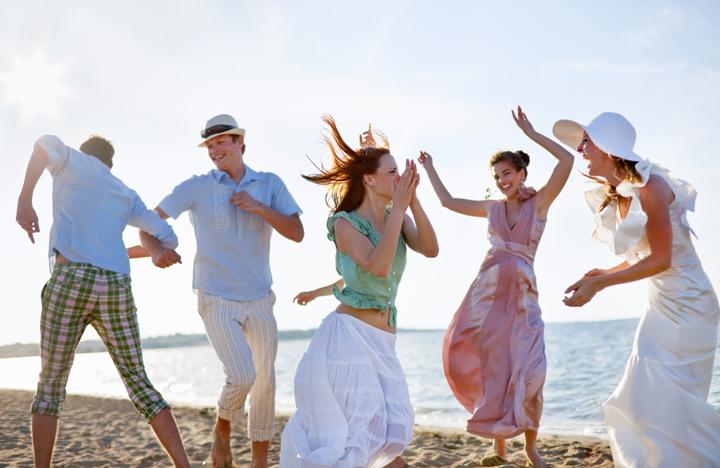 ビーチで踊る新郎新婦とゲスト