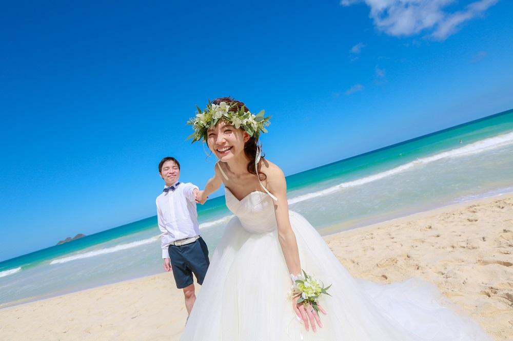 ビーチでドレス姿の花嫁がこちらを振り返っている