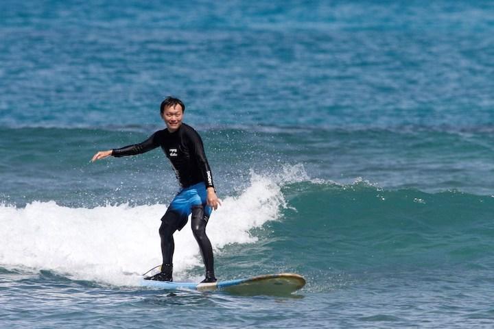 新郎、初めてのサーフィン体験で波にのる