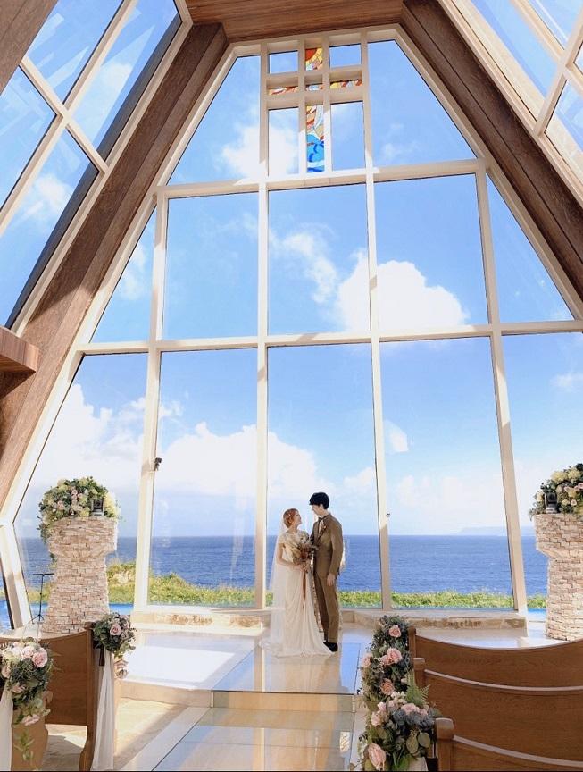 ガラス張りで海が一望できる祭壇を背にみつめあうふたり