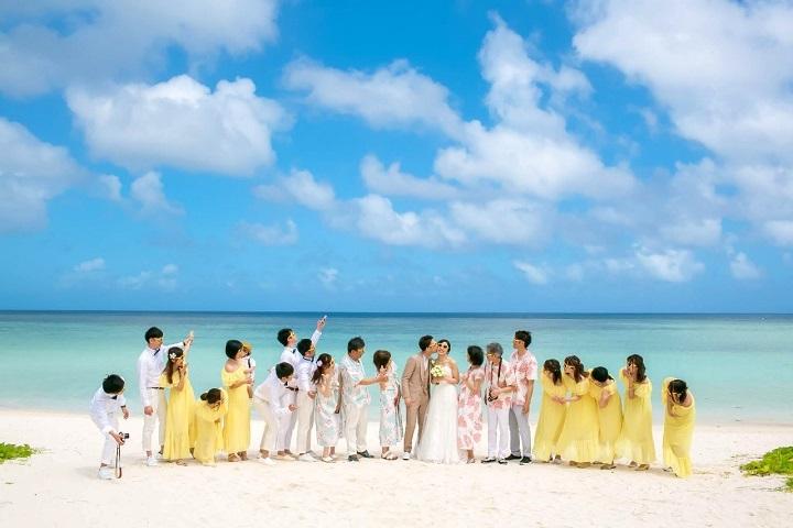 20人ゲスト全員とふたりが白砂ビーチで一列に並んで真ん中の新郎が新婦にキスしている