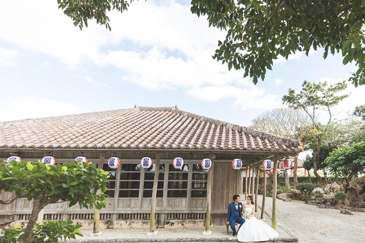 沖縄らしい瓦屋根の民家の軒先でウエディング姿のふたりが見つめあう