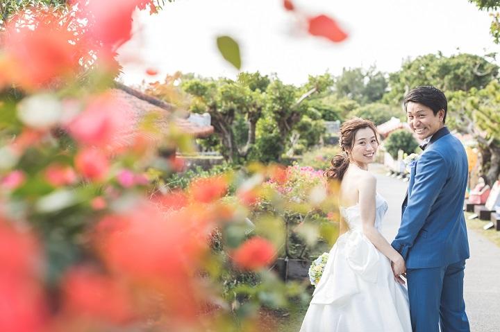 ハイビスカスの赤い花の生垣の道で振り向き笑顔のウエディング姿のふたり