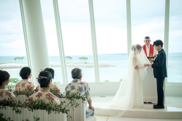 ガラス越しに海が一望できる祭壇で愛を誓うふたり