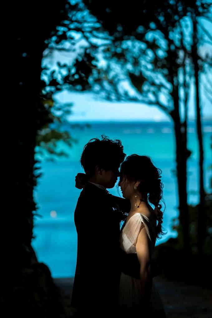 海の青が強調されてふたりは暗くシルエットで顔を寄せ合うドラマティックな写真