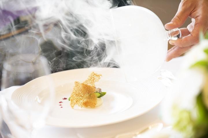 ガラスのフタを開けた瞬間、煙がふわっと料理の皿から上がっている瞬間