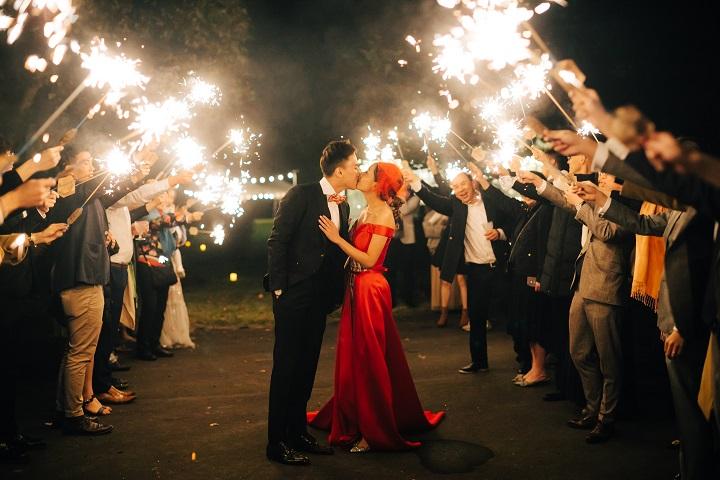 花火を手にしたゲストがふたりを囲み、赤いドレスの花嫁と黒いタキシードの新郎がキスをしている