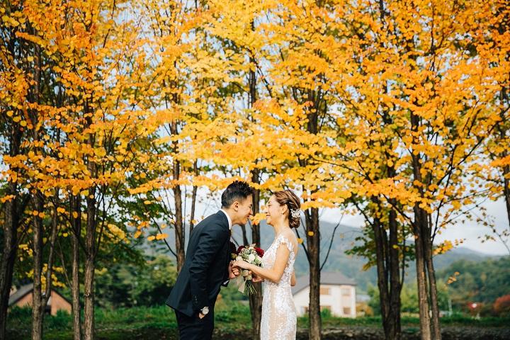 オレンジに紅葉した木々の前で見つめあうウエディング姿のふたり