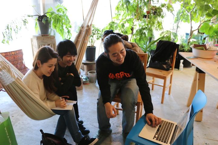 建築デザイナーを始め、パワフルな仲間たちと実行委員会を結成。写真はハンモックに座るふたりが、建築デザイナーの案内するパソコン画面を見ているところ