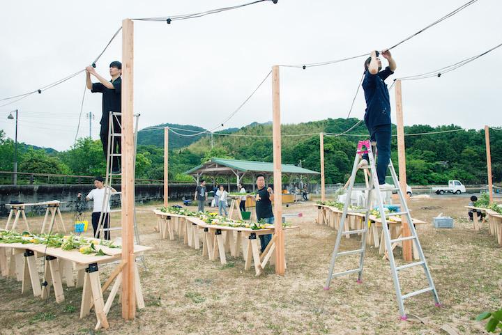 式当日の午前中、ビーチに備え付けた柱に電飾などをセッティングするスタッフ。テーブルには農家から仕入れたレモンを飾って
