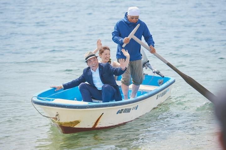 船で登場する父と娘。ビーチで待つゲストに大きく手を振っている